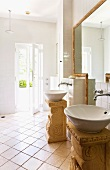 Two round sinks on free standing, Roman style pedestals in a light and bright bathroom with an entrance to a garden area