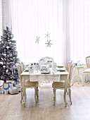 Rococo-style chairs and table with place settings in front of Christmas tree