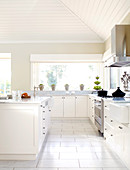 White kitchen with central kitchen island below sloping ceiling