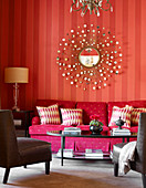Corner of living room with red striped wallpaper and decorative, sun-shaped mirror above deep pink sofa