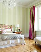 Traditionelles Schlafzimmer in zarten Pastelltönen; pinkfarbene Akzente in Vorhängen und Bettkopfende sorgen für Fröhlichkeit