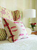 Bolster and decorative pillows in red and white on a bed with a white bedspread