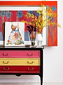 Vase of flowers and pictures on vintage chest of drawers with drawers of different colours against wall