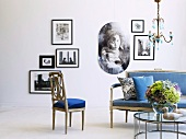 Antique sofa set with blue upholstery and modern coffee table with glass top in front of framed photographs on wall