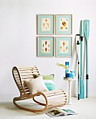 Rocking chair made from wooden slats and side table in front of blue wooden paddles leaning on wall next to gallery of pictures