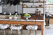 Long wooden kitchen table and chairs with curved metal frames in rustic kitchen