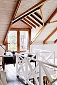 Workspace under sloping ceiling on gallery with white wooden balustrade