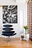 Retro designer armchair in front of modern artwork in corner of room