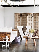 Rustic, wooden coffee table in front of sofa on castors and screen against partition wall