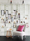 Small, upholstered armchair with cushion and side table against white, designer shelving unit