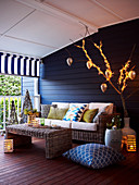 Wicker coffee table and sofa against blue-painted wooden wall on veranda