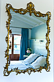 Wall-mounted mirror with floral, gilt ornamented frame reflecting bed in front of French windows with blue curtains