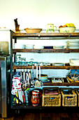 Crockery, baskets and hanging kitchen utensils on vintage wooden shelving