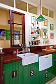 Retro kitchen with wooden worksurface and green-painted base units on interior wall with transom windows