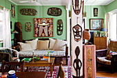 Cosy living room with antique furniture and African woodcarvings on green-painted walls