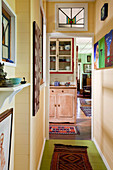 View along narrow corridor through doorway to rustic dresser in open-plan interior