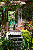 Bushes and grasses in front of wooden house with wicker armchair on sunny veranda