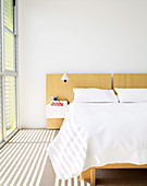 Sunlight shining through blinds into bedroom with double bed and white bed linen