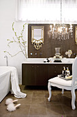 White Rococo chair and chandelier with glass ornaments in front of modern washstand with brown base unit in designer bathroom