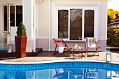 Relaxing by the pool - deckchairs and side table on side of pool in front of Mediterranean villa