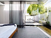Designer bedroom with airy curtains at partially glazed facade with view of pool in sunny courtyard