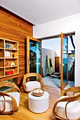 Unusual wicker chairs and small side table in front of open terrace doors in modern setting