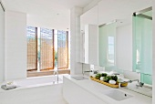 Purist bathroom with double washstand and bathtub in front of screen of swivelling wicker panels