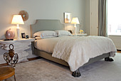 Bedside table in rough stone effect next to French bed with wall mounting and claw feet in postmodern bedroom