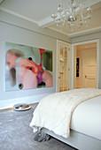 Französisches Bett mit postmodernen Klauenfüssen und moderne Kunst an der Wand in elegantem Schlafzimmer