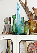 Decorative bottles of different colours and toys on top of vintage cabinet