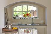 Kitchen counter in arched niche below window