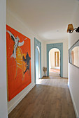 Long hallway with wooden floor, arched doorways and artworks on walls
