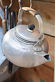 Old kettle hanging from hook