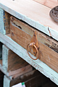 Wooden drawer with rusty handle in wooden shelving