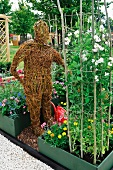 Life-sized straw figure of a human between flowerbeds