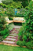 Secluded seating area in garden with wooden bench and cushions
