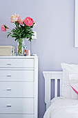 Vase of flowers on white chest of drawers next to bed against lilac wall