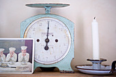 Post card in front of a vintage scale and candlestick holder and candle on a shelf