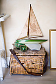 Basket with lid and old model ship on the floor