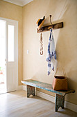 Open cloakroom with hat and towel hanging from a wall coat rack above a rustic wooden bench in a simple foyer