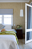 Ladies straw hat on a bed in front of window and open terrace doors in a simple bedroom
