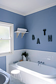Corner of a country style bathroom with built in bath tub in front of a window and bright blue wall