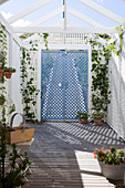 Garden shed made from white lattice panels and plant pots on the wooden floor