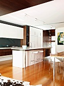 Modern kitchen with white cupboards and free-standing counter in open-plan interior