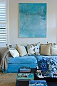Türkisfarbene Couch unter Aquarellbild im selben Farbton; davor ein blauer Hortensienstrauss auf dem Couchtisch