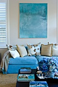 Various scatter cushions on sofa upholstered in light blue below picture on wall and behind flowers on coffee table