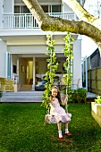 Girl sitting on swing hanging from tree in front of modern house