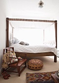 Wooden canopy bed in ethnic bedroom with wooden armchair