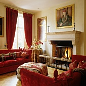Two red Knole sofas and animal-skin print ottoman in front of classic fireplace