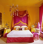 Bold candy colours and canopy bed in bedroom with Oriental touch